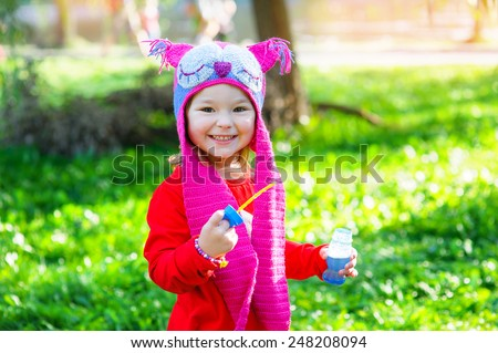 Portrait of happy little girl in the park in the header of an owl. - stock photo
