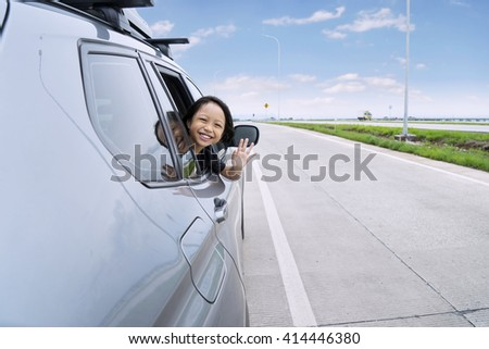 Portrait of happy little girl is sticking her head out the car window and waving hand on the camera - stock photo