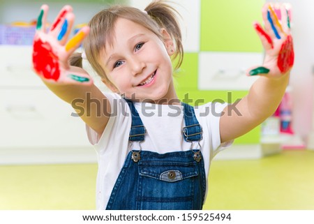 Portrait of happy little girl with colorful pains on hands