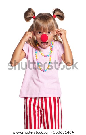 Portrait of happy little girl with red clown nose, isolated on white background. Child making grimace - funny monkey face.