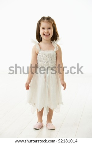 Portrait of happy little girl (4-5 years) wearing ballet costume looking at camera, smiling. Studio shot over white background. - stock photo