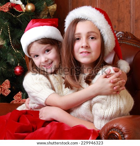 Portrait of happy little girls in Santa cap sitting over decorative Christmas tree/European caucasian little sisters
