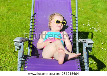 Portrait of happy little kid relaxing outdoors. Cute toddler girl wearing sunglasses enjoying hot summer day lying in sunbed in the park or garden. - stock photo