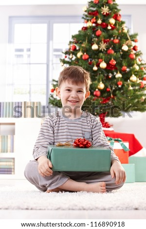 Portrait of happy little kid sitting in pyjama in christmas morning holding gift parcel, smiling at camera. - stock photo