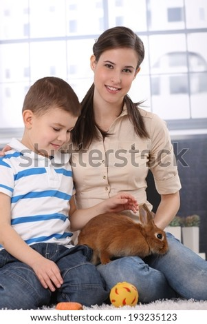 Portrait of happy little kid with mum caressing cute rabbit pet, smiling.