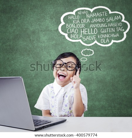 Portrait of happy little student imagine multi language of Hello on the cloud speech with laptop on the table