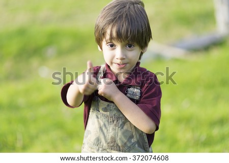 Portrait of happy lovely boy showing thumbs up - stock photo