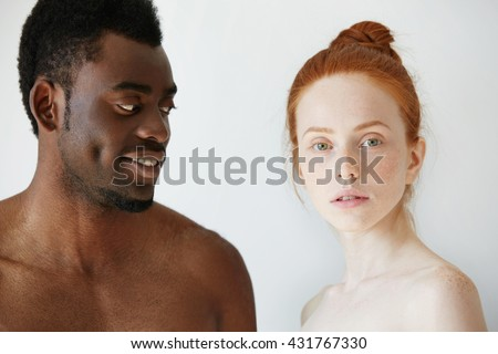 Portrait of happy loving interracial couple: shirtless African man looking at his nude redhead Caucasian girlfriend with love and affection, while she is standing next to him and looking at the camera - stock photo