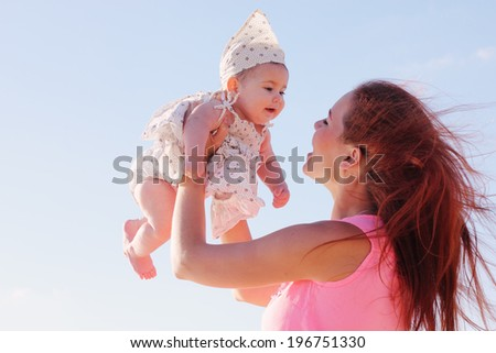 Portrait of happy loving mother and her baby outdoors - stock photo