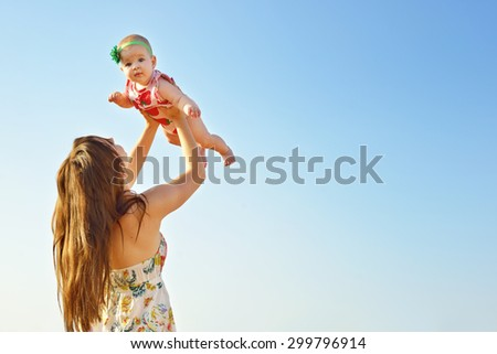 Portrait of happy loving mother and her baby outdoors. Mother and child against summer blue sky. - stock photo