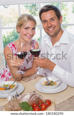 Portrait of happy loving young couple with wine glasses sitting at dining table at home - stock photo