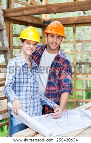 Portrait of happy male and female architects examining blueprint at construction site