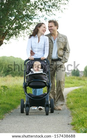 Portrait of happy male and female parents walking with their child in baby carriage  - stock photo