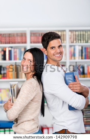 Portrait of happy male and female students holding binders while standing back to back in library - stock photo