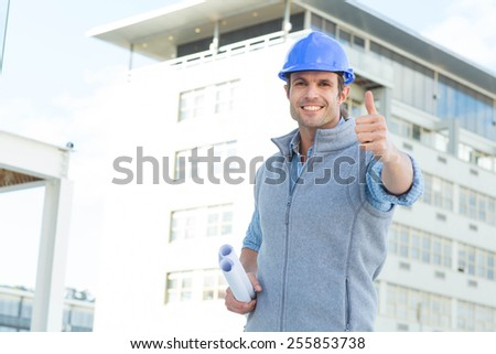 Portrait of happy male architect gesturing thumbs up outside building - stock photo