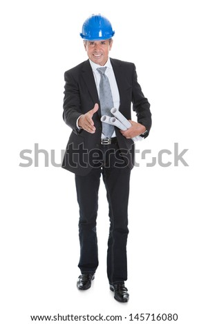 Portrait Of Happy Male Architect Offering Handshake And Holding Blue Print - stock photo