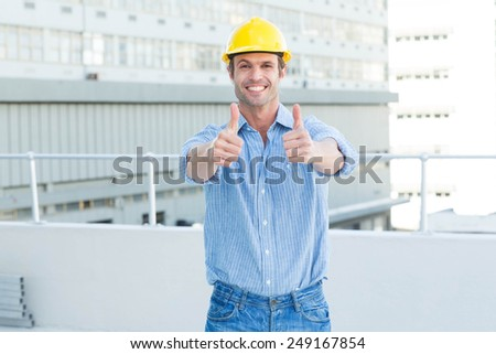 Portrait of happy male architect showing double thumbs up outdoors - stock photo