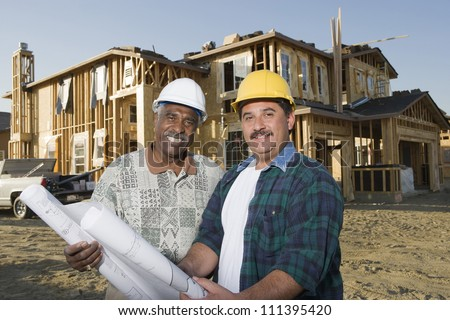 Portrait of happy male architects with blueprint in front of incomplete house - stock photo