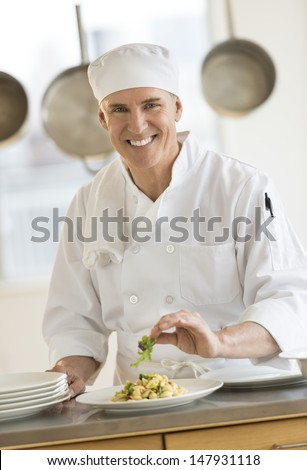 Portrait of happy male chef garnishing pasta dish in commercial kitchen - stock photo