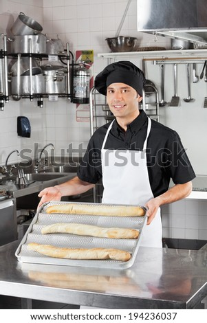Portrait of happy male chef presenting loafs in industrial kitchen