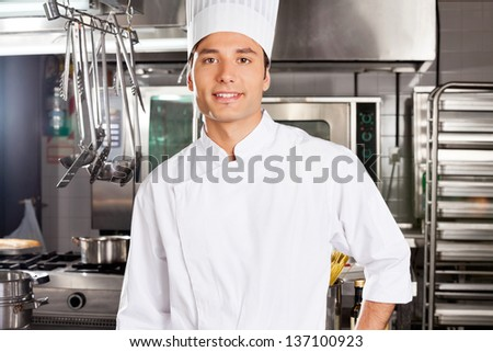 Portrait of happy male chef standing in commercial kitchen