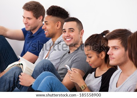 Portrait of happy male college student sitting with classmates against wall in classroom - stock photo