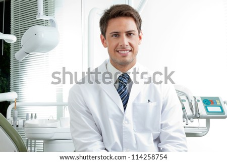 Portrait of happy male dentist wearing lab coat while sitting in clinic - stock photo