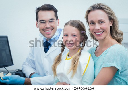 Portrait of happy male dentist with assistant and little girl