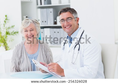 Portrait of happy male doctor and female patient in clinic - stock photo