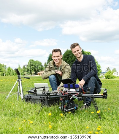 Portrait of happy male engineers with laptop and digital tablet by UAV at park - stock photo