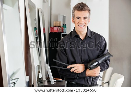 Portrait of happy male hairstylist with hairdryer and straightener standing at salon - stock photo