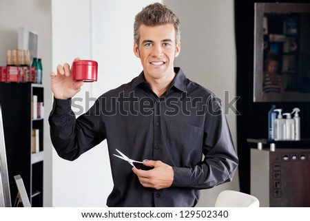 Portrait of happy male hairstylist with scissors presenting hairgel bottle at salon - stock photo