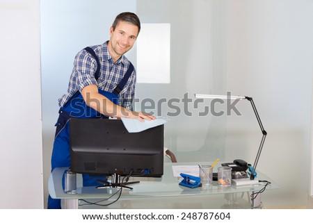 Portrait Of Happy Male Janitor Cleaning Desktop In Office - stock photo