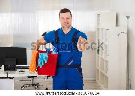 Portrait of happy male janitor showing thumbs up while carrying bucket in office - stock photo