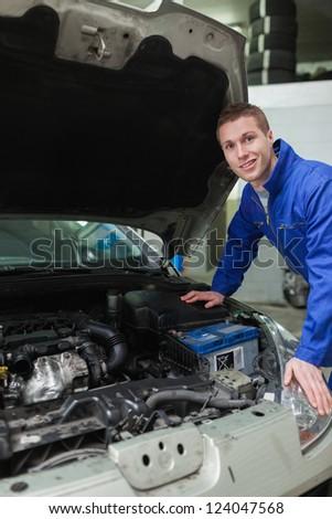 Portrait of happy male mechanic repairing  car engine - stock photo