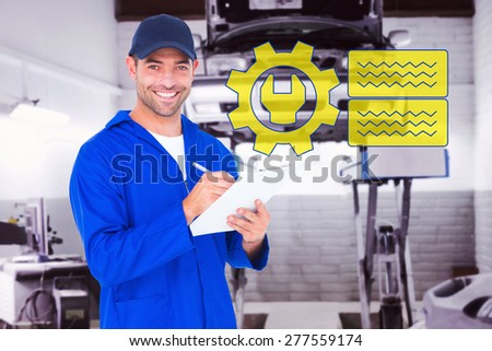 Portrait of happy male mechanic writing on clipboard against auto repair shop - stock photo