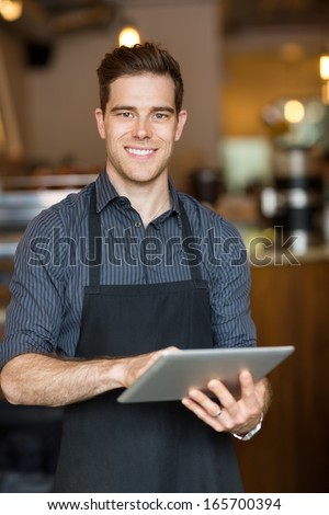 Portrait of happy male owner holding digital tablet while standing in cafe - stock photo