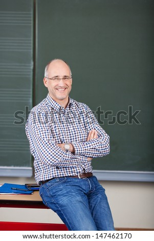 Portrait of happy male professor with arms crossed sitting on desk in classroom - stock photo