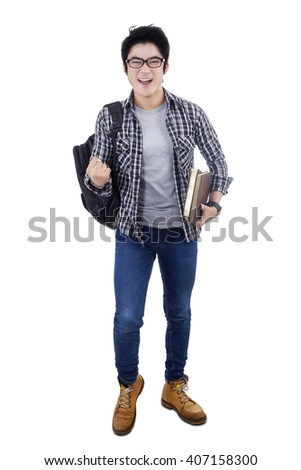 Portrait of happy male student expressing his success in the studio, isolated on white background - stock photo