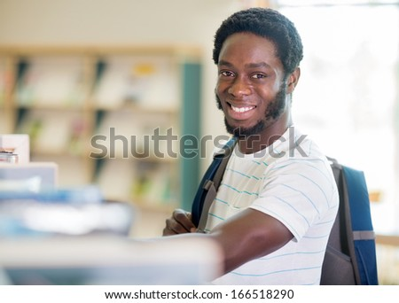 Portrait of happy male student with backpack in bookstore