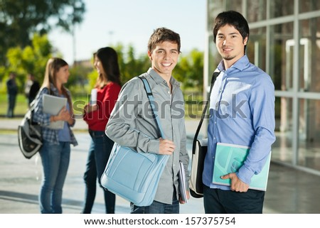 Portrait of happy male students with friends standing in background on college campus