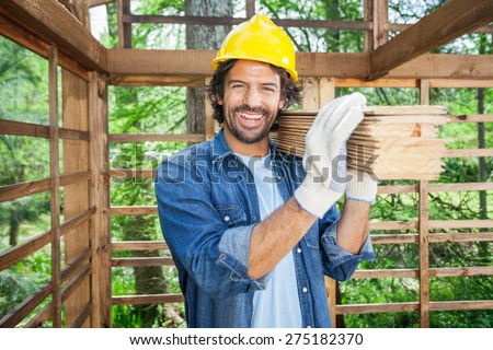 Portrait of happy male worker carrying wooden planks on shoulder at construction site - stock photo