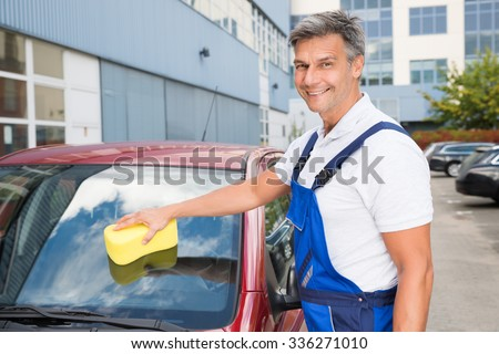 Portrait of happy male worker cleaning car windshield with sponge - stock photo