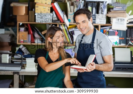 Portrait of happy male worker holding book while colleague pointing at it in factory