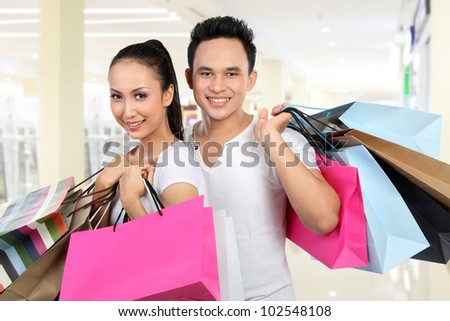 portrait of happy man and woman carrying shopping bag at the mall - stock photo
