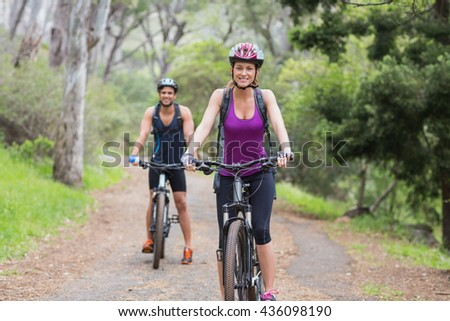 Portrait of happy man and woman riding bike in forest