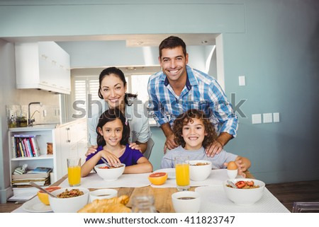 Portrait of happy man and woman with children having breakfast at home