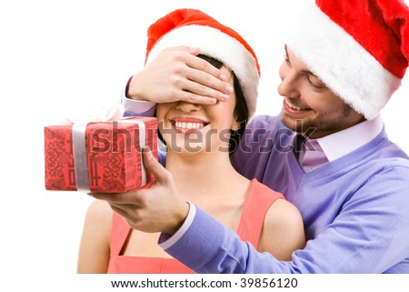 Portrait of happy man closing female?s eyes by his hand while holding giftbox before her - stock photo