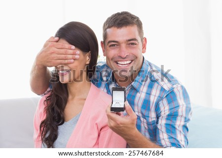Portrait of happy man covering womans eyes while gifting ring at home - stock photo