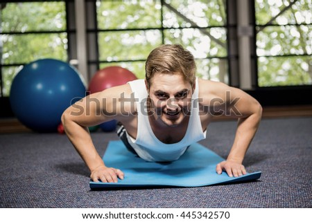 Portrait of happy man doing push ups at gym - stock photo